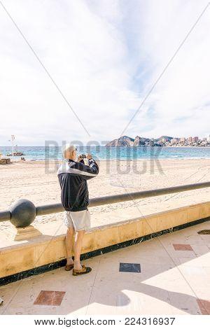 Benidorm, Spain - January 14, 2018: Elderly tourist taking photo of Benidorm, Costa Blanca, Spain.