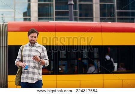 Young man drinking a coffee and sending a text message on a cellphone while standing near a bus stop on a street in the city