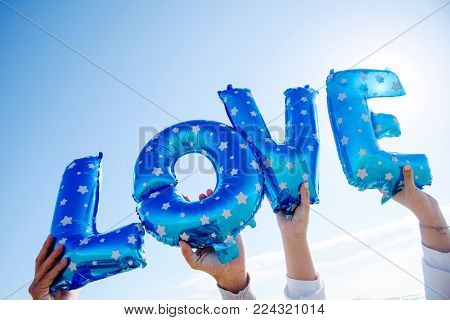 closeup of the hands of a man and a woman holding some blue letter-shaped balloons forming the word love against the blue sky