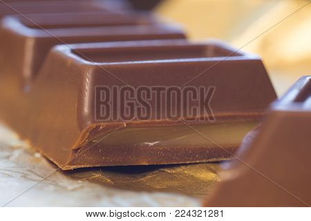 Photo of milk chocolate bar with stuffing on foil, close-up