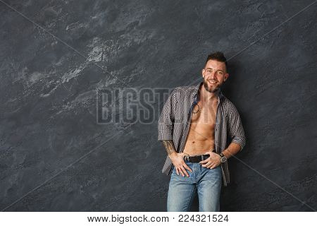 Handsome smiling man with athletic body posing in studio. Fashion boy on grey background, studio shot, copy space