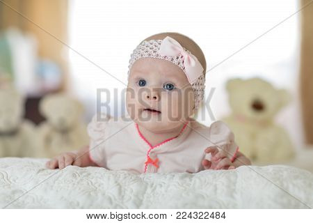 Baby girl lying in bed at home