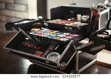 Case of professional makeup artist with cosmetic and tools on table indoors