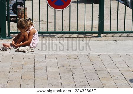 Funny girl sitting on the ground and zippers sandals