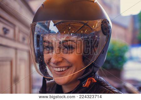Cute young woman wearing a moto helmet.