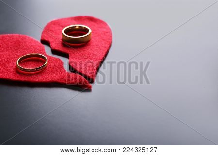 Fabric heart cut in half with wedding rings on grey background. Relationship problems