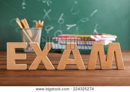 Word EXAM made of wooden letters on table