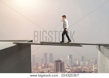 business man tries to cross an improvised bridge between two buildings
