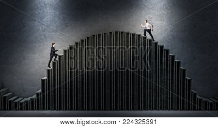 two businessmen compete to get to the top of the stair