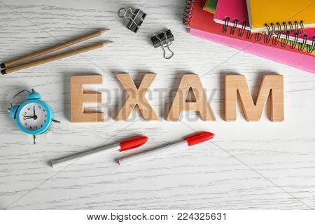Word EXAM made of letters and stationery on wooden background