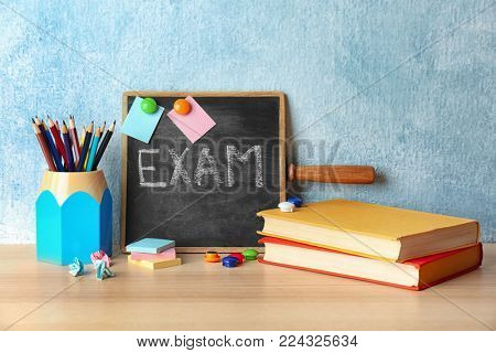 Blackboard with word EXAM, notebooks and pencils on table