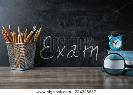 Holder with pencils, notebooks and word EXAM written on chalkboard