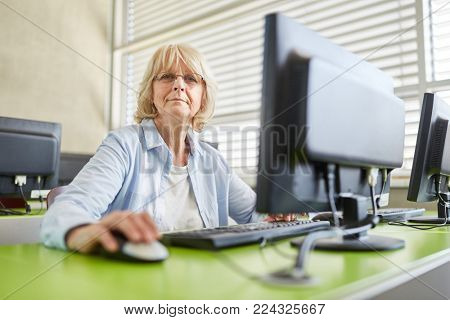Senior woman with computer in IT class learning and training