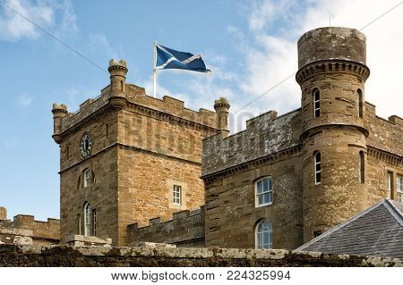 Calzean estate, Ayrshire, Scotland, UK: July 25, 2015 -Towers of Calzean castle with Scottish flag waving in the breeze, Scotland, UK