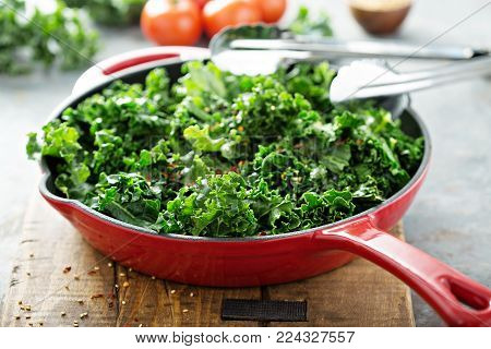 Quickly sauteed kale with chili flakes in a cast iron pan, healthy cooking concept