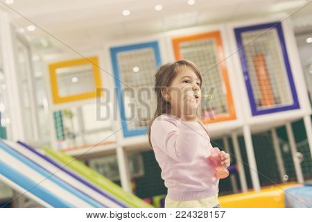 Cute little girl playing in a playroom, making a soap bubbles
