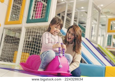Mother and daughter playing in a colorful playroom, having fun while daughter is playing with giant pink caterpillar swing. Focus on the daughter