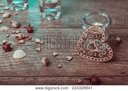 Spa concept in Valentine's Day, candles, handmade heart, seashells, dry roses. Rustic style. Toned image in chocolate, aquamarine tones. Healthy Concept