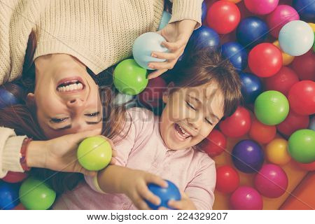 Top view of cheerful mother and daughter playing in a pool filled with colorful balls. Focus on the daughter