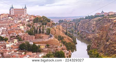 Panorama of Old city of Toledo with Alcazar and river Tajo at dusk, Castilla La Mancha, Spain