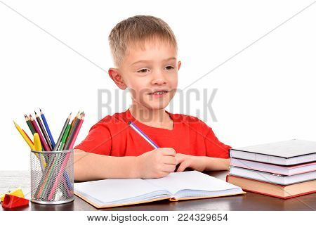 The boy at school. The boy is doing homework. Homework for the schoolboy. The teenager writes in the notebook. A good student. A boy with books.