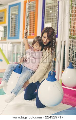Mother holding her daughter while she is happily enjoying swinging on a giant ball in a playroom