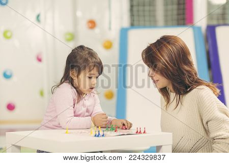Mother and daughter sitting in a playroom, playing a ludo game and enjoying their time together