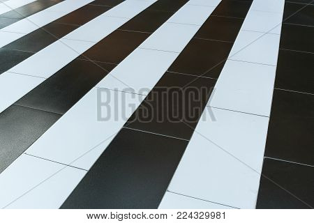 Close-up abstract diagonal pattern of alternating black and white stripes of tiles on the floor.  Perspective view.