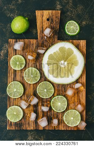 Lime cut into slices on a cutting board with ice. Cool refreshing photo with citrus fruits. Top view