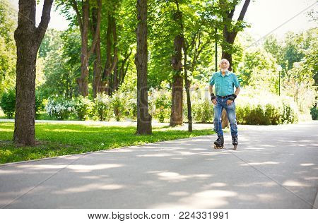 Active old age. Happy senior man roller skating outdoors. Elderly man enjoying sports in sunny summer park . Healthy lifestyle concept, copy space