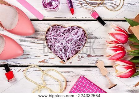 Cute gift for crush. Heart-shaped box beside pump shoes, nail polishes, bijou and flowers.