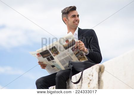 Cheerful handsome businessman analyzing newspaper while resting outdoors. Positive purposeful young male analyst reading last news during stroll. Strategy concept