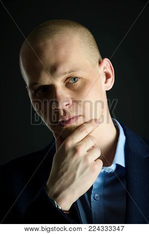 Closeup portrait of thoughtful man in suit being worried about something on black background.