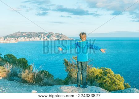 Happy kid enjoying holiday by Mediterranean sea in Benidorm, Costa Blanca, Spain.