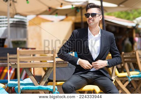 Jolly confident businessman buttoning jacket while sitting at table in sidewalk cafe. Pensive fashionable tourist resting in summer cafe. Or cheerful manager preparing for informal meeting. Successful man concept