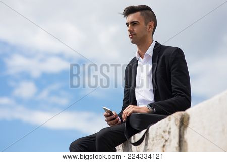 Pensive handsome guy imaging future while resting on pier. Dreamy ambitious young businessman sitting on stone and looking into distance, contemplating nature. Deep in thoughts concept