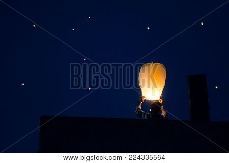 Silhouette of man flying paper sky lantern shot against a sky filled with lanterns. These lanterns have become traditional during the festival of makar sankranti in Rajasthan india