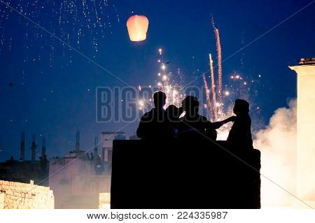 Silhouette of people standing on a roof with fireworks and sky lanterns in the background. Shot during the indian festival of makar sankranti or uttaryan in india