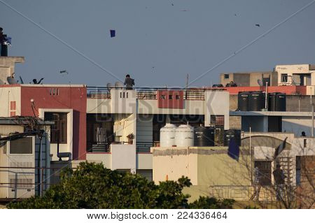 Jaipur, India - 14th Jan 2018: People standing on rooftops and flying paper kites on Makar sankranti or uttaryan in india. Kite fighting is a traditional sport on this day