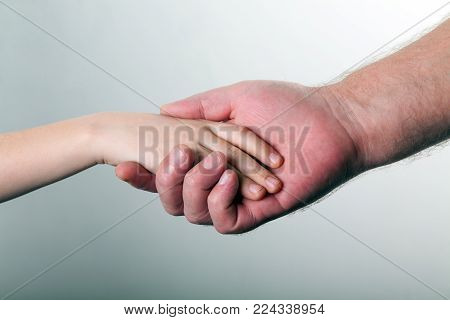 old man and kid holding hands together on gray background