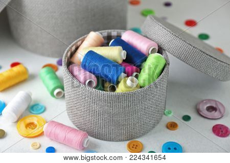 Box with color sewing threads and buttons on light background