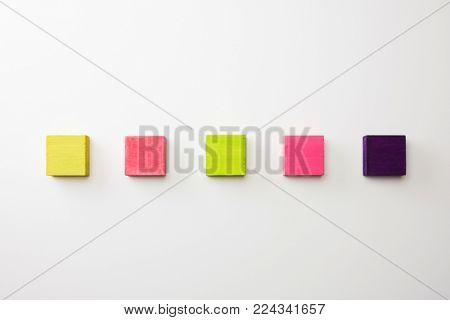 Index, menu or cover abstract back ground, consisting of five colored wooden blocks. On neutral white background, with highlight on upper left. vivid pink, green,purple.