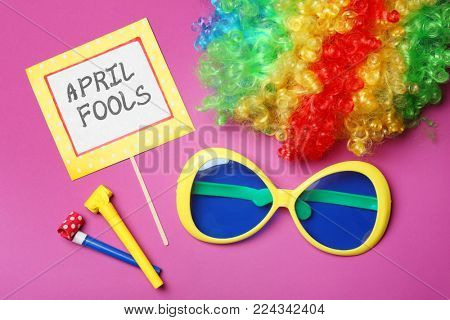Big glasses, party horns and rainbow wig on color background. April fool's day celebration
