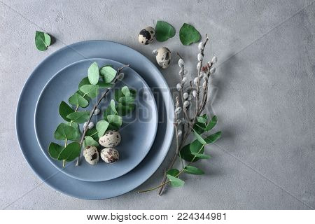 Eucalyptus and pussy willow twigs with quail eggs on plate as decor for Easter table setting