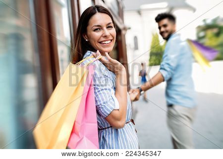 Happy attractive loving couple enjoy spending time in shopping together