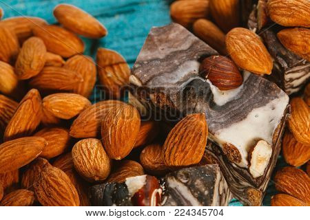 candy paste and almonds on blue wooden background.