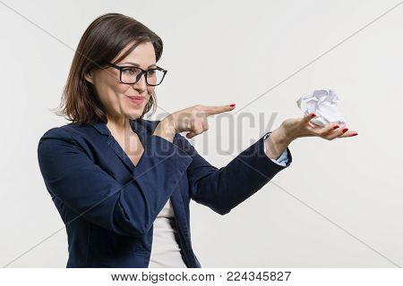 Woman holding a crumpled paper ball in her hand, with her finger down on the ball. White studio background. Getting rid of problems.
