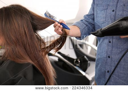 Professional stylist blow drying woman's hair in salon, closeup poster