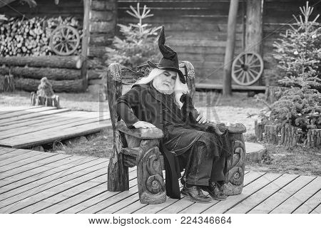 Old Man In Wizard Costume Hat For Halloween Strokes Black Cat And Sits In Wooden Chair On Natural Ba