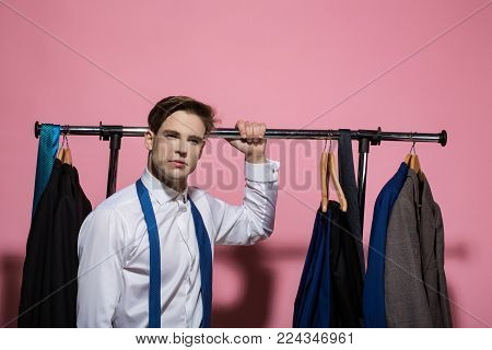 Business fashion, style concept. Man hold rack with jackets on hangers in wardrobe. Clothing, dressing, closet. Businessman in white shirt, blue necktie on pink background. Shopping, sale, purchase.